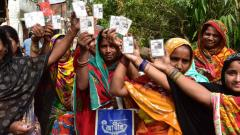 Women voters show their voter cards during their voting at polling booth in East Midnapore District in West Bengal on Sunday. ANI Photo