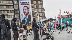 "Pedestrians walk past a poster with an image of Turkish President Recep Tayyip Erdogan which translates as ""Thank you Istanbul"" at Taksim Square in Istanbul on Friday"