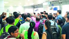 Passengers stranded at the airport wait for airport authorities to take help them.