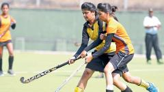 A player of St Clare's Girls High School, Camp, (right) in action against Anglo Urdu Girls High School