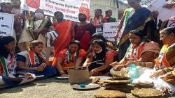 Protests against fuel price hikes; NCP women light a fire in front of the Collector's office.